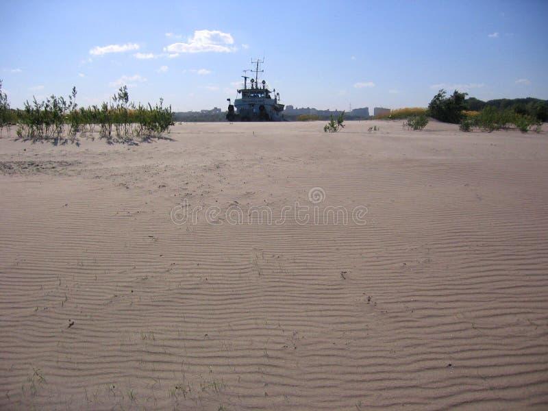 船的剪影反对含沙沙漠的在距离被看见 库存图片