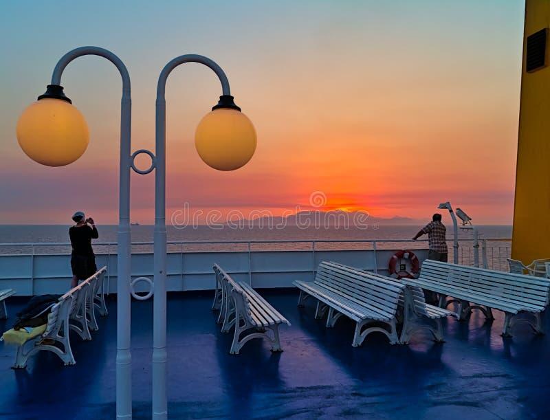 船的年轻女人,为日落照相,而太阳是在遥远的海岛山后, 图库摄影