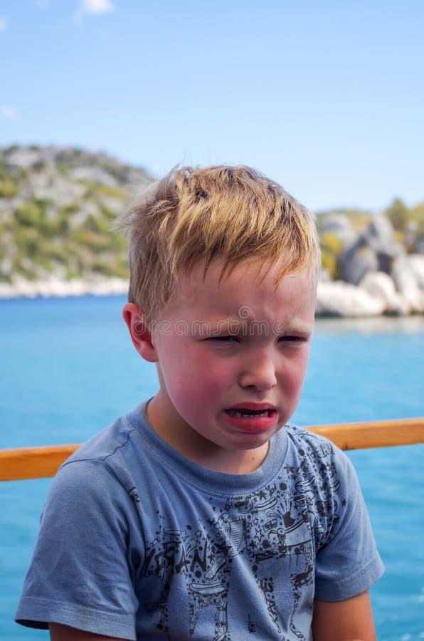 船的恼怒和哭泣的男孩在海 库存图片