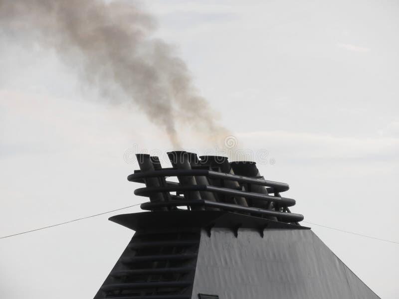 船集中散发在天空的黑烟 图库摄影