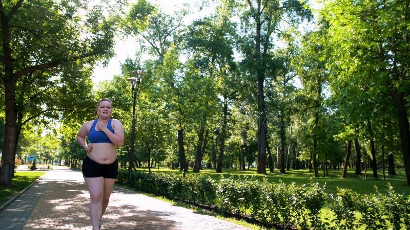 艰苦肥胖妇女对凹凸部,烧油脂的用尽的锻炼,不安全的翻倒女孩 免版税库存图片