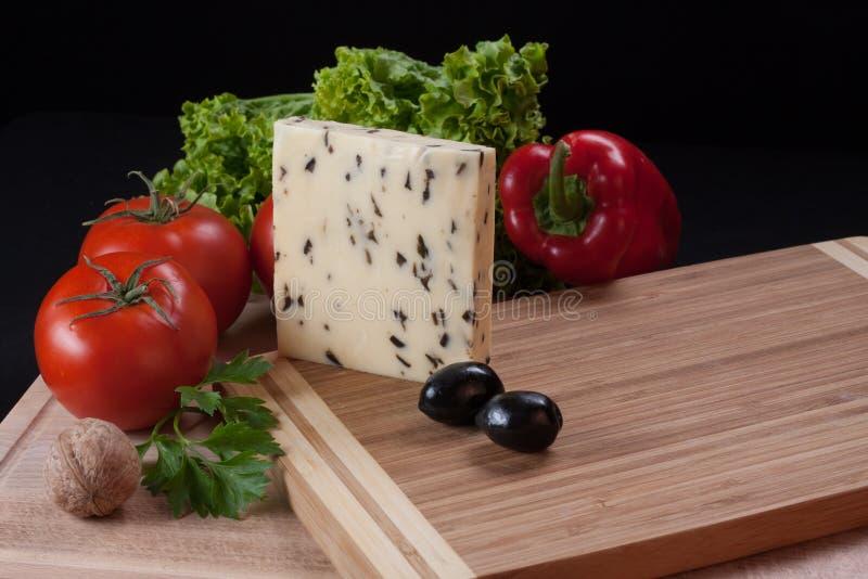 黄色乳酪用在切板的橄榄 库存图片