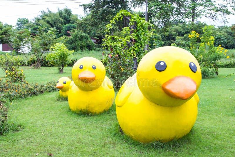 黄色低头在绿草的装饰雕塑 免版税库存图片