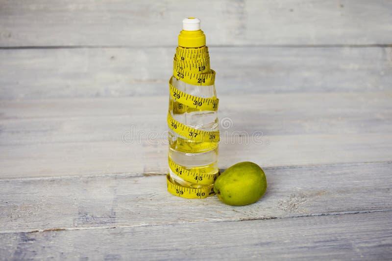 黄色卷尺和一个水瓶和苹果在白色木 库存图片