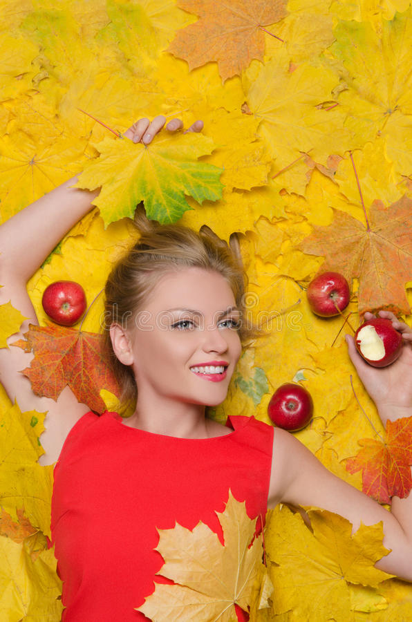 黄色叶子和苹果的美丽的妇女 免版税库存照片