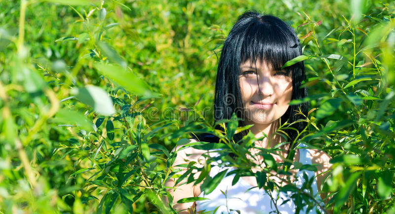 绿色叶子的美丽的女孩 免版税库存图片