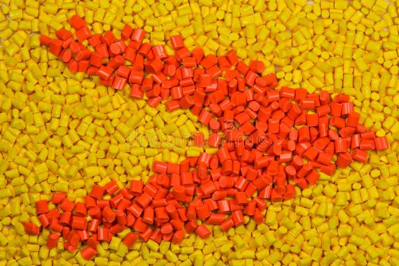 黄色和橙色塑料颗粒化 免版税库存照片