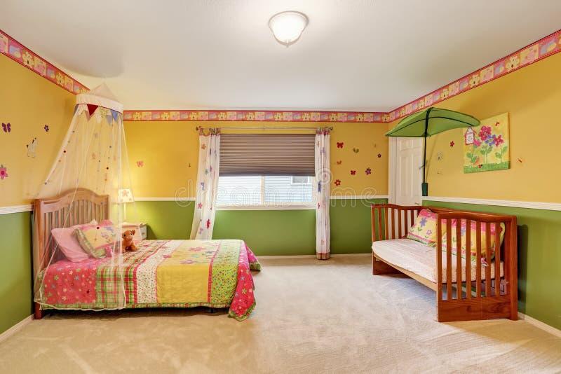 黄色和绿色口气的孩子卧室与地毯地板 图库摄影