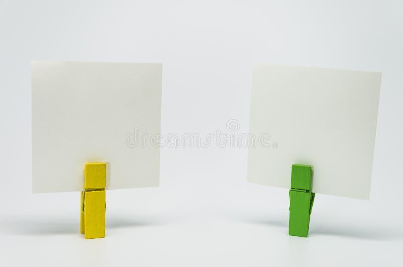 黄色和绿色木夹子夹紧的备忘录纸张有白色背景和选择聚焦 免版税库存照片
