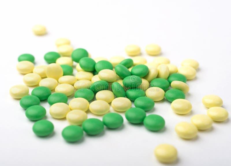 绿色和黄色医学药片堆  图库摄影