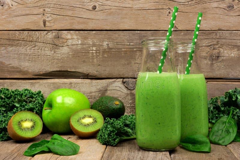 绿色圆滑的人用无头甘蓝、鲕梨、菠菜、苹果和猕猴桃反对土气木头 图库摄影