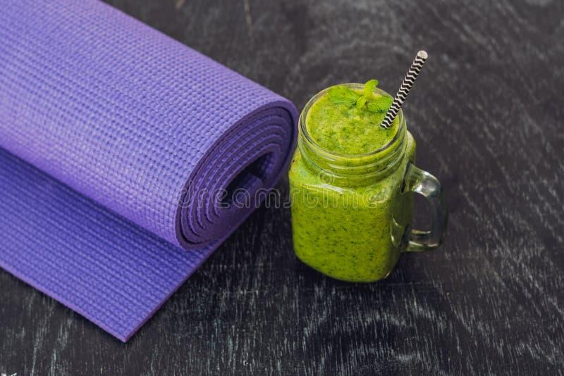 绿色圆滑的人由菠菜制成和菠萝和瑜伽席子 健康吃和体育概念 图库摄影