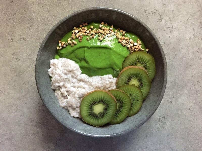 绿色圆滑的人碗用荞麦、猕猴桃和chia布丁 免版税库存图片