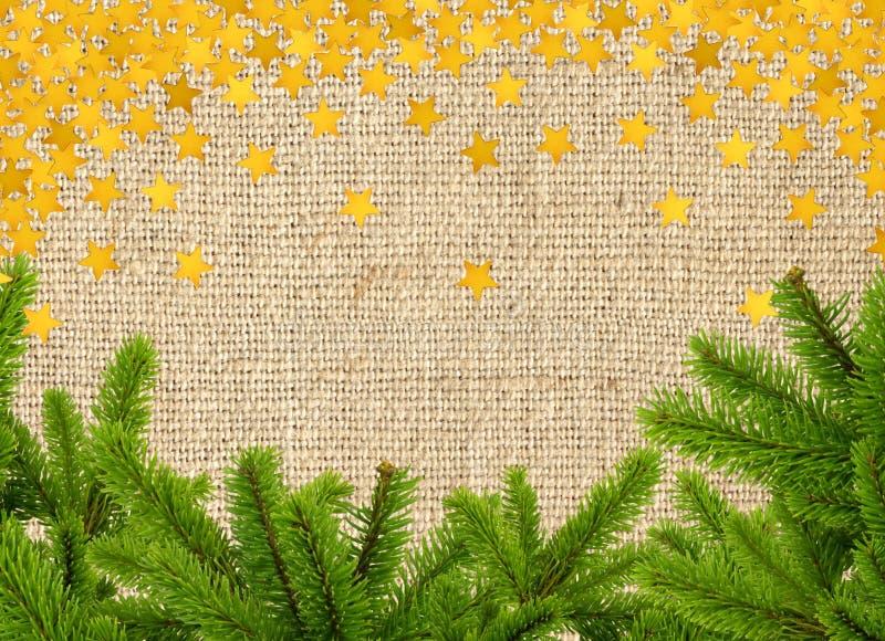 绿色圣诞树分支和金黄星在亚麻制纹理 库存图片