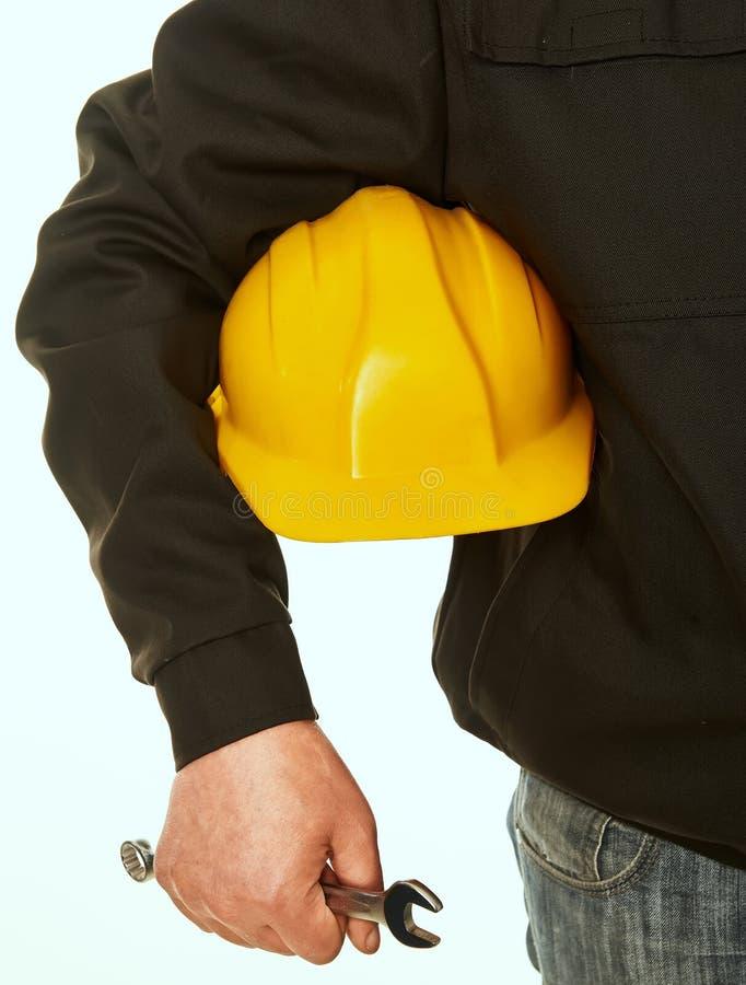 黄色安全帽和扳手手中工人 库存图片
