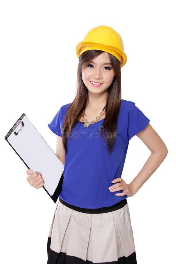 黄色安全帽的微笑的年轻建筑师妇女,在白色 免版税库存照片