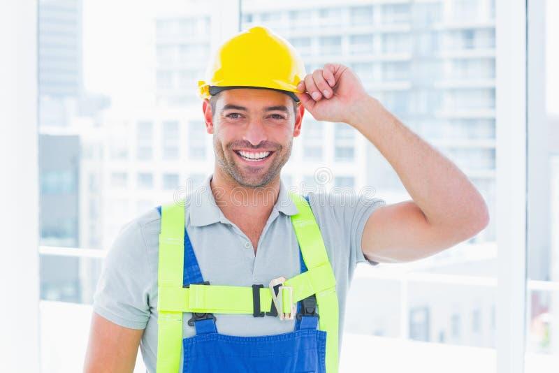 戴黄色安全帽的愉快的体力工人 库存图片