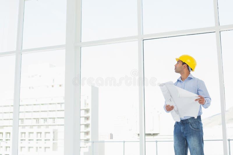 黄色安全帽的建筑师有看窗口的计划的 免版税库存照片