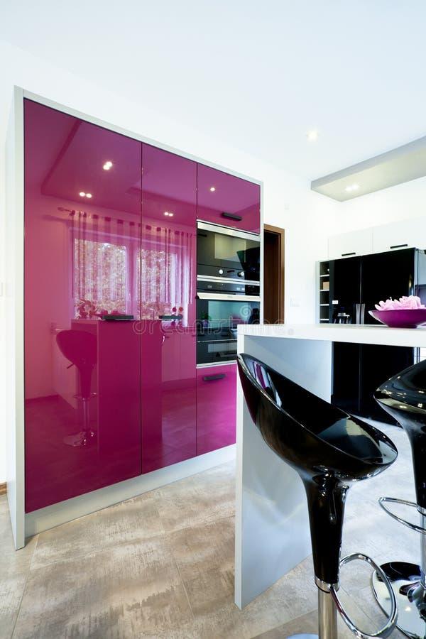 紫色家具在一个现代厨房里 库存图片