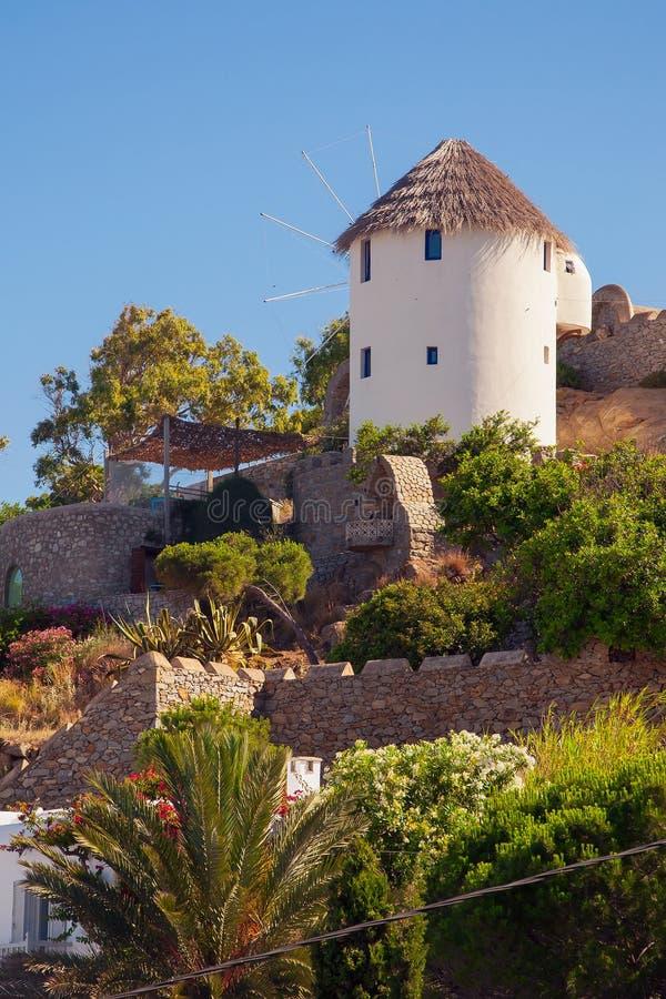 绿色山坡的旅馆与风车和庭院 免版税库存图片