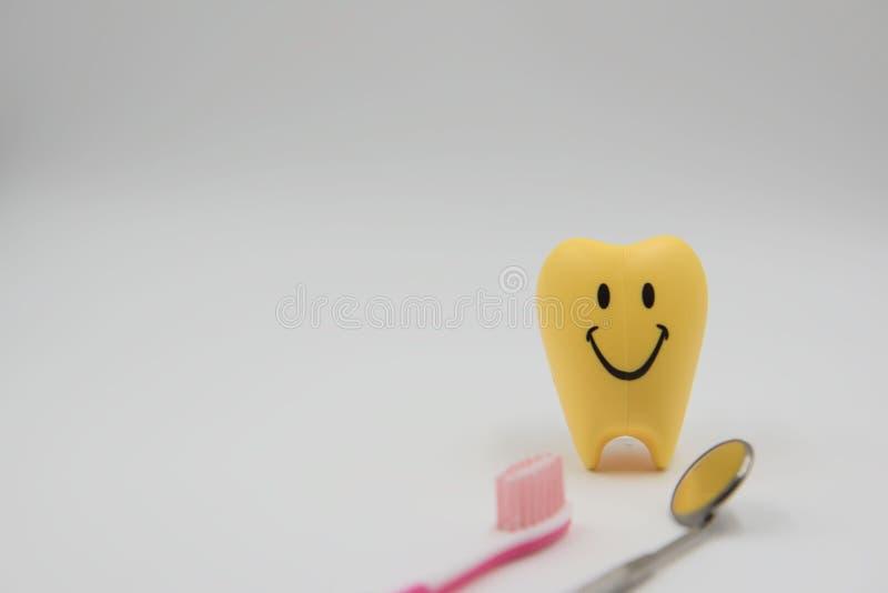 黄色式样微笑逗人喜爱的玩具牙在白色背景的牙科方面 免版税库存图片