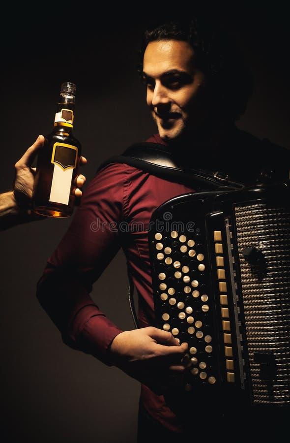 色彩手风琴球员和瓶酒精饮料 免版税库存照片