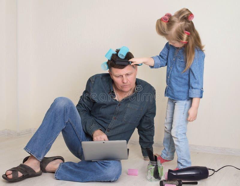 色彩缤纷的卷发小女孩,为父亲做风趣的发型 学龄前女孩梳着成年父亲的头发 免版税库存照片