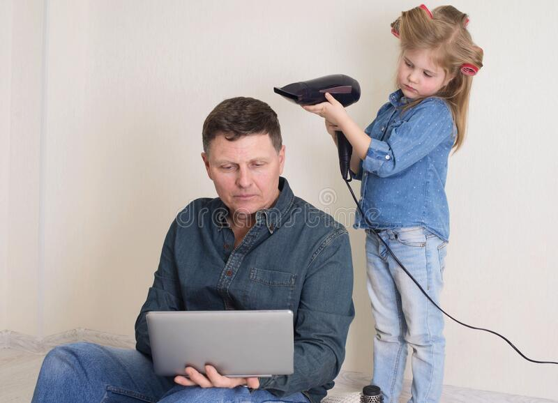 色彩鲜艳的卷发小女孩吹干父亲的头发 女儿梳着成熟父亲的头发,玩得好像在工作 库存照片