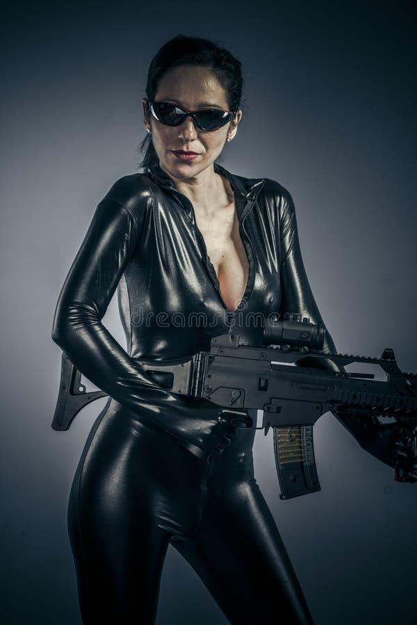 色情,性感的摆在与枪的女孩军事妇女。 库存图片