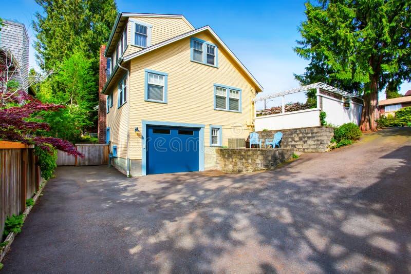 黄色房子外部有蓝色车库门和沥青车道的 免版税库存图片