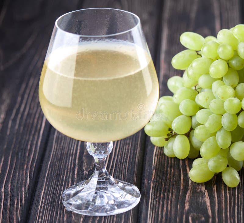 绿色新鲜的成熟葡萄和一杯白葡萄酒 免版税库存图片