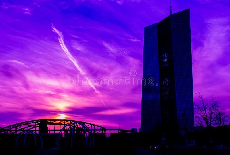 紫色日落背景的玻璃摩天大楼  图库摄影