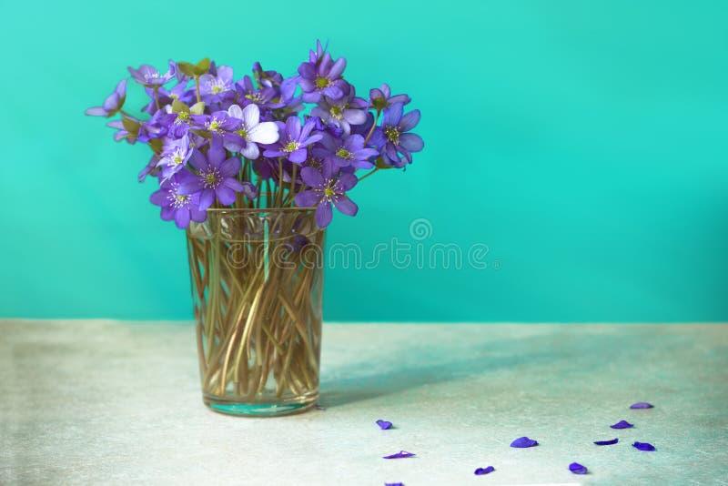紫色春天紫罗兰花束在玻璃的在窗口附近 免版税库存照片