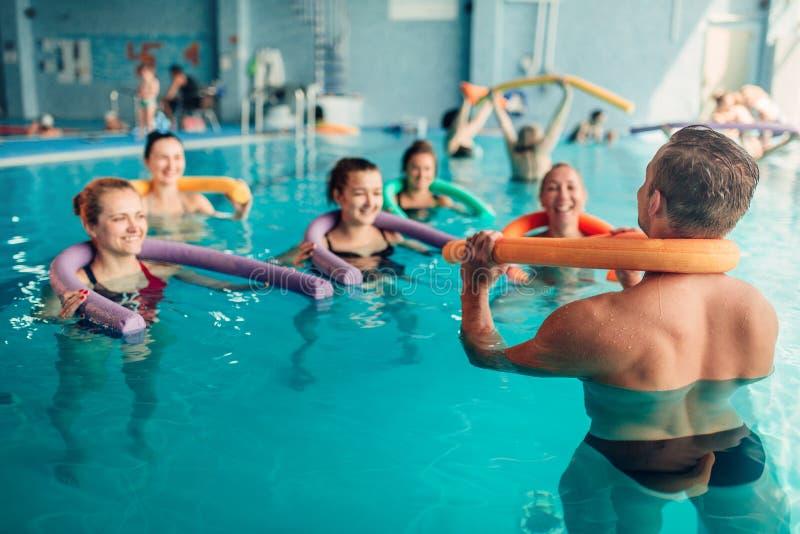 水色有氧运动行使,有男性教练员的妇女 库存照片