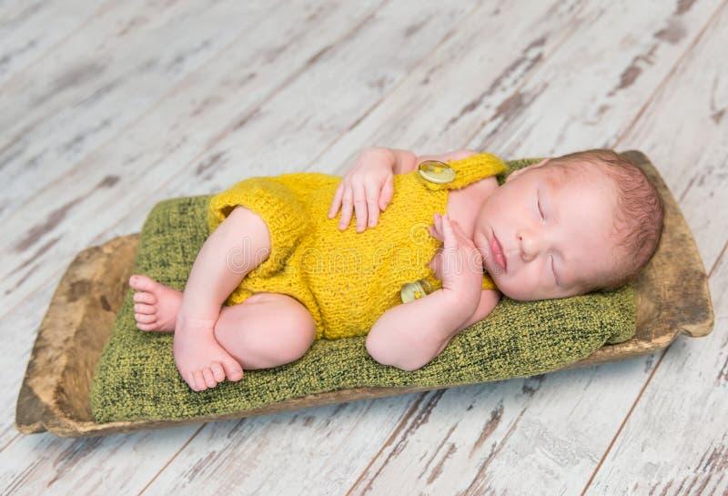 黄色服装的新出生的婴孩睡觉在木轻便小床的 图库摄影