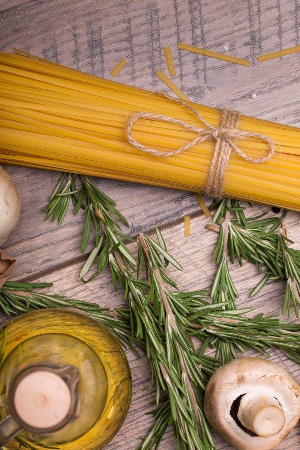 黄色未煮过的面团、蘑菇、鹌鹑蛋和迷迭香的宏观图片 在一张木桌上的未煮过的成份 免版税库存照片