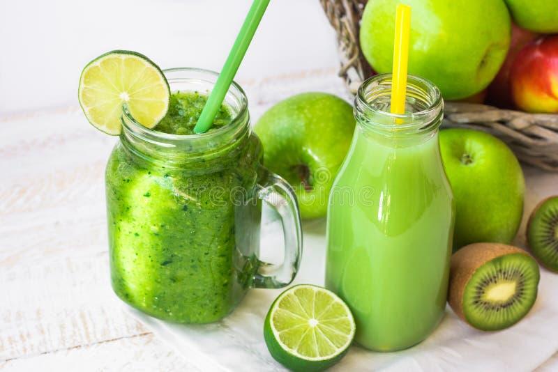 绿色果子和草本汁在瓶,菜圆滑的人在瓶子杯子,户外,夏天春天阳光斑点 免版税库存照片
