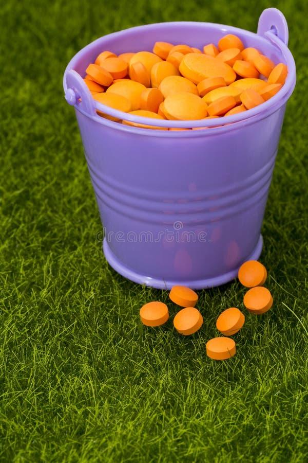 紫色桶被填装对边缘用站立在草的橙色药片 免版税库存图片