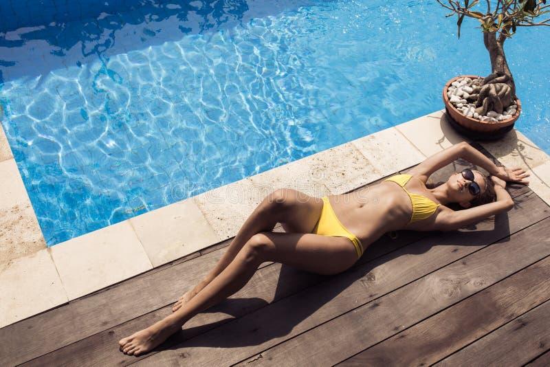 黄色比基尼泳装的晒日光浴年轻亭亭玉立的美丽的妇女 免版税图库摄影