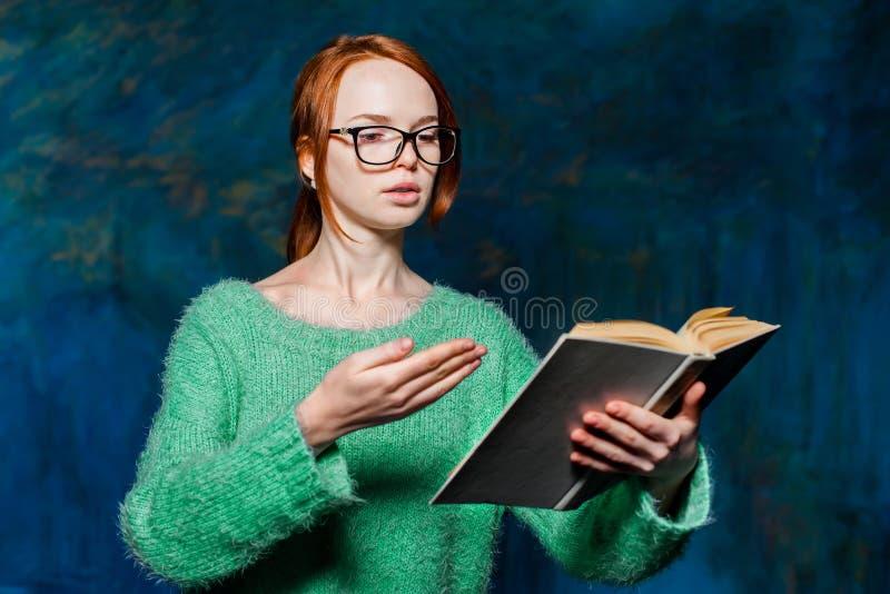 绿色毛线衣和玻璃的年轻红头发人女孩 免版税库存照片