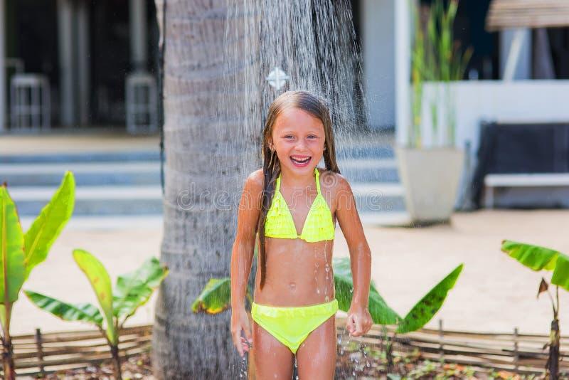 黄色游泳衣的美丽的愉快的小女孩在海滩的一场阵雨下在一个热带庭院里 免版税库存图片