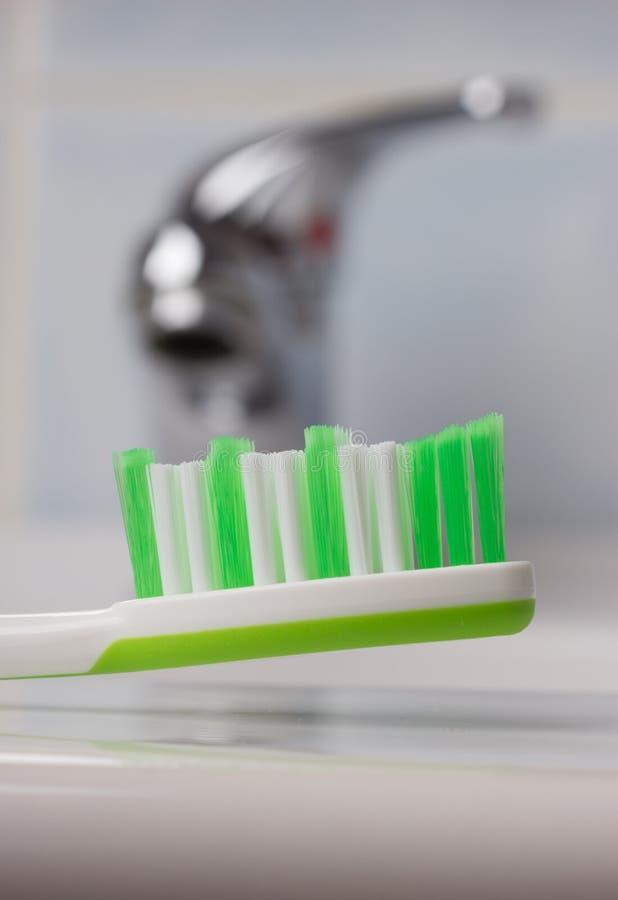 绿色牙刷在水槽的卫生间里 免版税库存图片