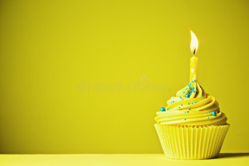 黄色生日杯形蛋糕 免版税库存照片