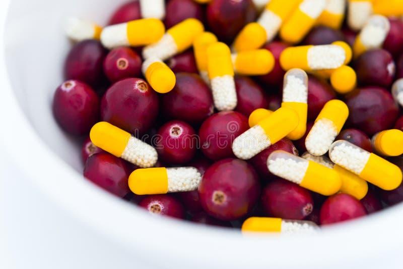 黄色白的药片和在碗的新鲜的蔓越桔的医疗混合 库存照片