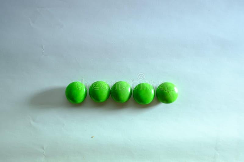 色的上漆的巧克力糖相似与在白色背景的M&M 库存照片