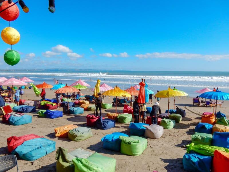 色的伞和lamzaks在巴厘语海滩以海浪为背景 免版税图库摄影