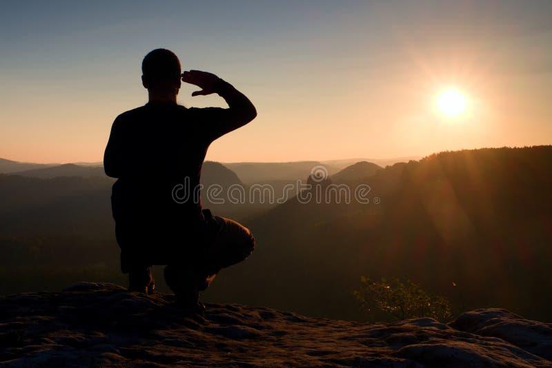黑色的单独运动员 蹲位置的高远足者享受看法在山峰的日落 免版税库存照片