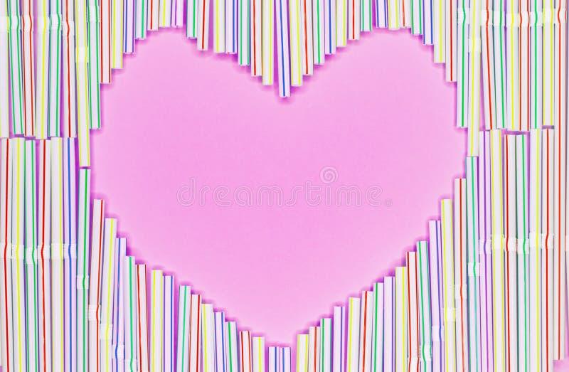 色的塑料秸杆或鸡尾酒小管心脏框架在浅兰的背景与拷贝spase 库存图片