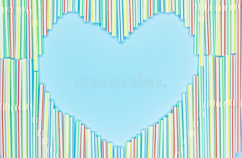 色的塑料秸杆或鸡尾酒小管心脏框架在浅兰的背景与拷贝spase 免版税图库摄影