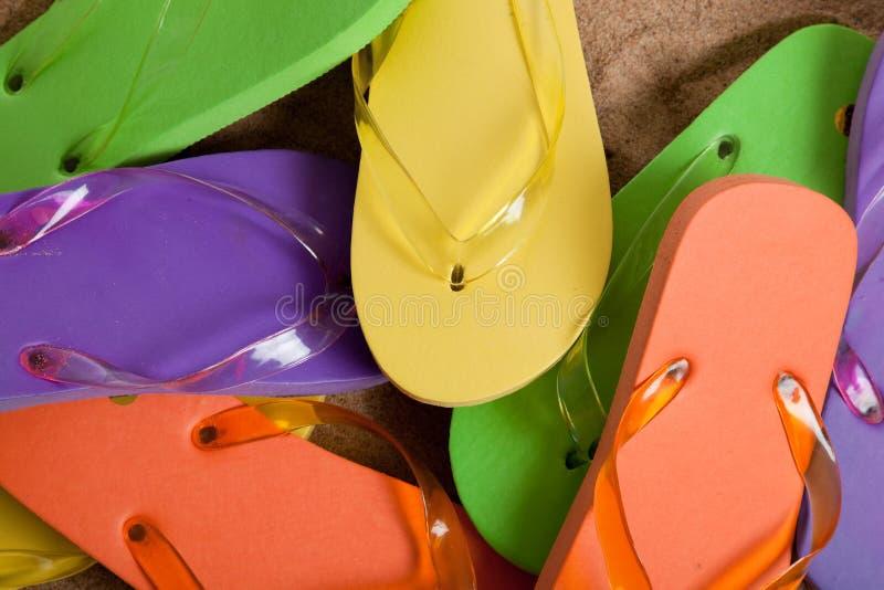 色的塑胶人字平底拖鞋铺沙多种 库存照片